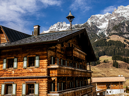 Traditionelles Holzhaus und Berge in Leogang